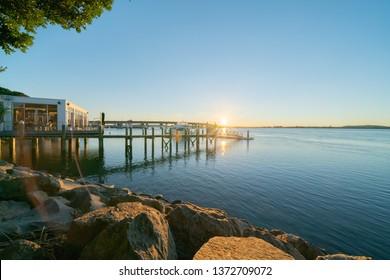 Sunrise  glows across Tauranga harbor with curving lines of harbor bridge and jetty through trees.