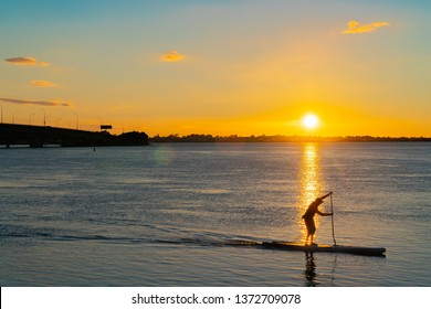 Sunrise  glows across Tauranga harbor with  curving lines of harbor bridge as silhouette of stand up paddleboarder passes.