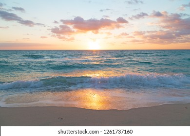 Sunrise with a golden reflection in foaming wave. Sandy ocean beach at sunrise in Miami Beach, Florida, USA.