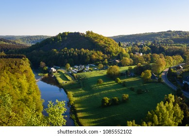 Sunrise in Herbeumont village with castle of Herbeumont on top of hill and campsite along riverside river Semois. Houses on countryside hills. Luxembourg province, Ardennes region, Wallonia, Belgium.