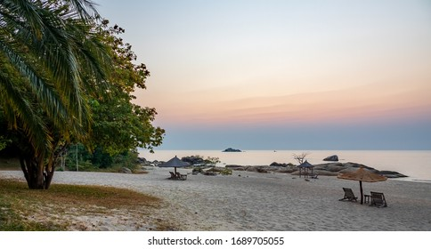 Sunrise at idyllic beach in lake malawi with pink sky and text space