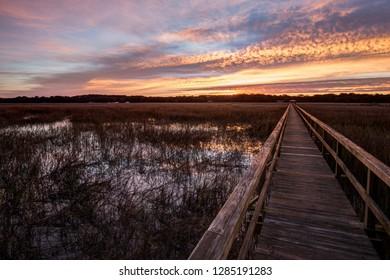Sunrise illuminates a long dock over the salt marsh grasslands on St. Helena Island outside of Beaufort, SC.