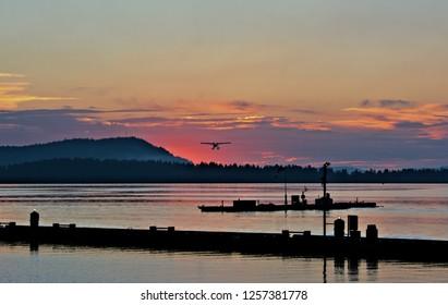 Sunrise inner harbor low clouds color range illumination horizon nature background silhouette mountain range fishing pier seaplane sky background