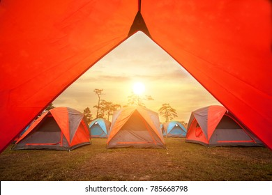 Sunrise inside a Tent,Tourist tent in camp in the mountain, Looking out of open tent door upon green meadow and forest in morning sunshine