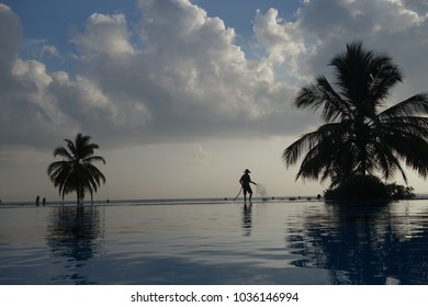 Sunrise at island paradise, swimming pool, early morning at beach resort, sun coming up on vacation, dramatic clouds, palm trees silhouette, man with hose silhouette, blue still water reflecting light