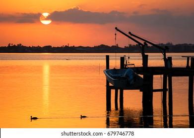Sunrise at the Jensen, FL Docks as some ducks go by.