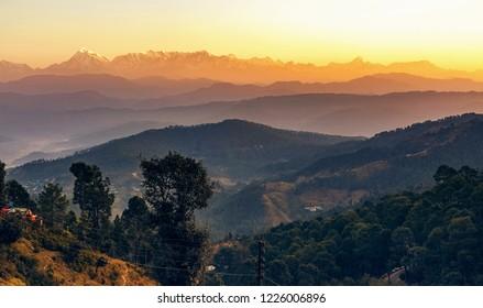 Sunrise at Kausani Uttarakhand India with scenic view of adjacent mountain ranges with Himalaya snow peaks.