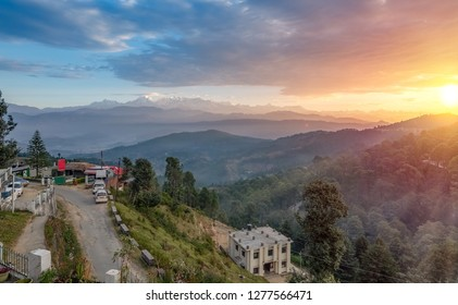 Sunrise at Kausani Uttarakhand with view of mountain road and distant Garhwal Himalaya range with snow peaks.