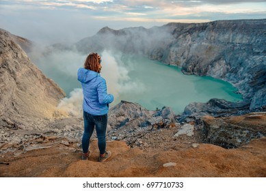 Sunrise at Kawah Ijen,indonesia.Sulfur mines view point.People look at sulfur mines.Women standing volcano views.Women are raising hands