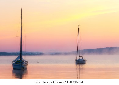 Sunrise at lake Ammersee with boats on a misty morning