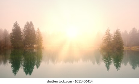 Sunrise at a lake on a foggy morning