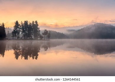 Sunrise at lake with reflections at water. Foggy landscape at low light.