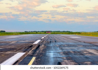 Sunrise with landscape airport of wet runway with traces of rubber tires on asphalt