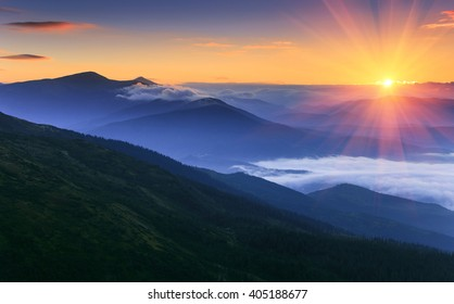 Sunrise landscape of foggy and cloudy mountain valley.