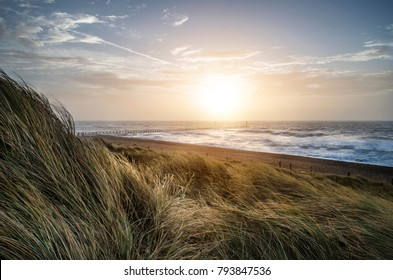 Sunrise landscape image of sand dunes system over beach with wooden boardwalk