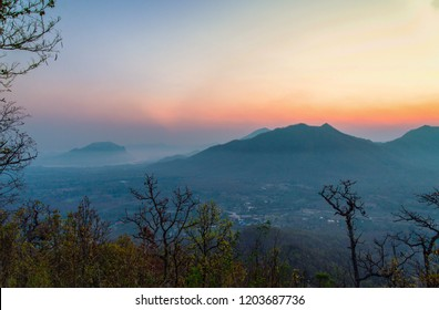 Sunrise landscape mountain scene in the morning village background orange and blue sky view on hill with tree foreground