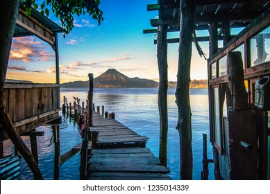 Sunrise landscape travel photo of lake Atitlán in Guatemala.  View from wooden pier over water with view of volcano on the horizon.
