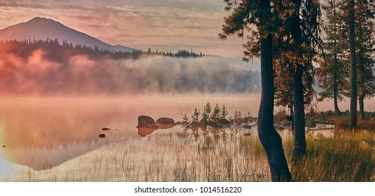 Sunrise and light fog rising off of Elk Lake in the Deschutes National Forest in the summer