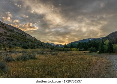Sunrise light hits the clouds at a rural ranch in Idaho.