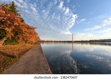 Sunrise light warms the colorful autumn landscape on the National Mall in Washington, D.C. The Washington Monument is reflected in the waters of the Tidal Basin. Beautiful cirrus clouds fill the sky.