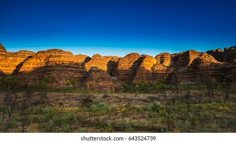 Sunrise lighting up the banded sandstone domes of the southern face of the Bungle Bungle Massif in the World Heritage Listed Purnululu National Park in the remote Kimberley region of Western Australia