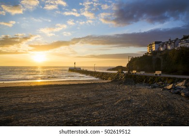 Sunrise at Looe beach with clouds in the sky and golden colours, Cornwall, UK