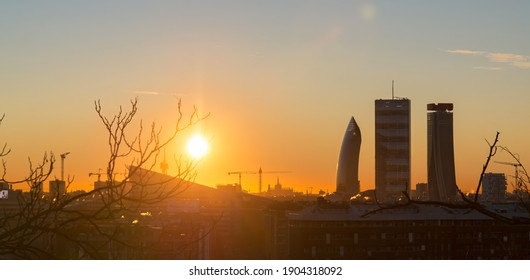 Sunrise in Milan (Italy) in backlight, with lens flares and perfect blue sky. Silhouette of towers of Citylife district in the background.