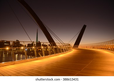 Sunrise Modern design lit Arched bridges at entrance of Elizabeth Quay marina, new tourist attraction in Perth, Western Australia, bell tower in background.