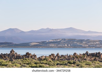 Sunrise at Mono Lake with hazy pastel colored mountains in the background.