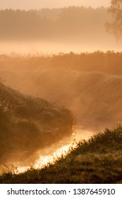 Sunrise and morning mist over a stream