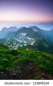 Sunrise mountain panorama from Brienzer Rothorn with purple sky, Switzerland.
