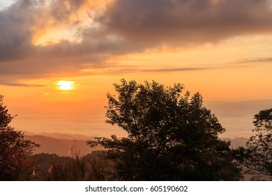Sunrise at mountain terrain in a sea of mist, on cloudy sky. Beautiful panoramic view of highland.