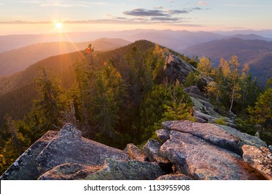 Sunrise in the mountains. Autumn landscape with a rocky ridge. Spruce forest and stones