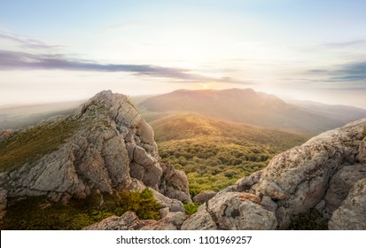 Sunrise in the mountains of Crimea - panoramic landscape overlooking the plateau Karaby with Demerdzhi: sun, sea, forest and sky