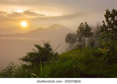 Sunrise in mountains with green tropical trees in a morning haze on the foreground