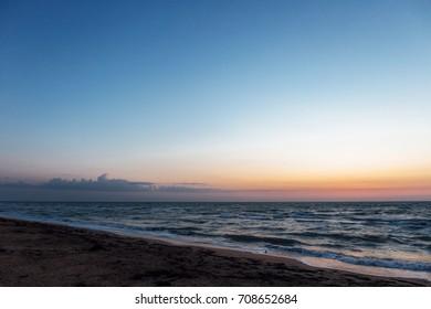 Sunrise near the sea beach with blue waves