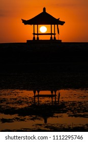 Sunrise on the beach with Sun can seen through the hut. with the reflection of the hut on the water- wonderful Sunrise background - Sanur Beach Bali