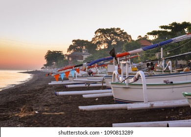 Sunrise on a black sandy beach covered by traditionl balinese boats: jukung