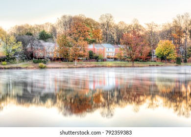 Sunrise on Braddock lake in Burke, Virginia, USA, Fairfax county with reflection of townhouses, fog, mist on water surface in autumn and orange trees
