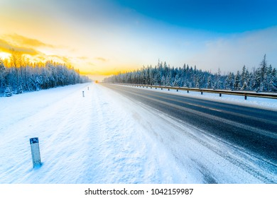 Sunrise on a clear winter morning, the headlights of approaching cars on a country road into a snowfall passing through a pine forest. View from the side of the road. Russia, Europe. Beautiful nature.