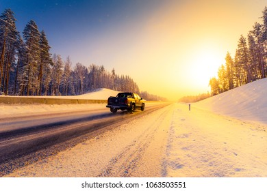 Sunrise on a clear winter morning, pickup rides on the highways in the snow. View from the side of the road. Coniferous forest. Russia, Europe. Beautiful nature. Orange-purple toning.