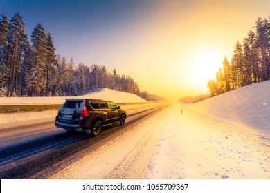 Sunrise on a clear winter morning, the car rides on the highways in the snow. View from the side of the road. Coniferous forest. Russia, Europe. Beautiful nature. Orange-purple toning.