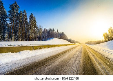 Sunrise on a clear winter morning, empty highways in snow. View from the road. Coniferous forest. Russia, Europe. Beautiful nature.