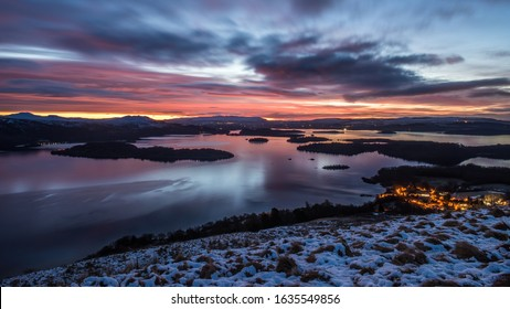 Sunrise on a cloudy, winter morning over the village of Luss and Loch Lomond as seen from the slopes of Beinn Dubh, Scotland.