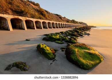 Sunrise on a coast. Concrete arches of city waterfront, seaweed covered stone in foreground. Washed out sandy beach. Peaceful, quiet and warm morning.