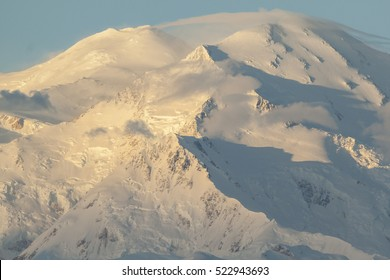 Sunrise on Denali as high winds form a lenticular cloud, Denali National Park, Alaska.
