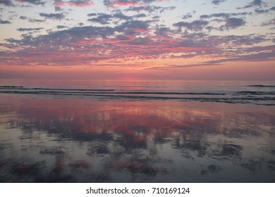 Sunrise on an East Coast Beach - Pink and Purple Clouds - Partly Cloudy Sky - Waves Crashing