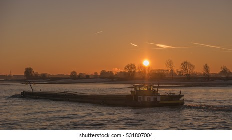 Sunrise on a foggy morning by the Waal river with inland ship sailing on the water, Nijmegen Netherlands December 2016,inland ship, binnenvaart , cargo transport