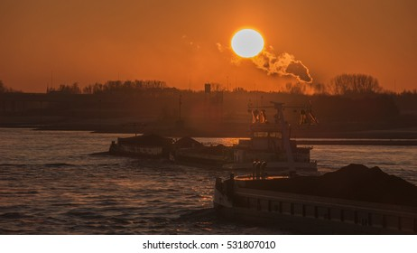 Sunrise on a foggy morning by the Waal river with inland ship sailing on the water, Nijmegen Netherlands December 2016,binnenvaart Sunrise inland shipping,
