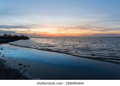 Sunrise on the horizon above a lake with beach in the Green Heart of the Netherlands, Europe. Reeuwijkse Hout.
